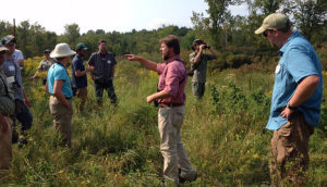A Cornell Lab of Ornithology biologist discusses young forest habitat suitable for Golden-winged Warblers at the Grand Lake Reserve during the St. Lawrence Valley Partnership Habitat Management Workshop. / Ashley Dayer